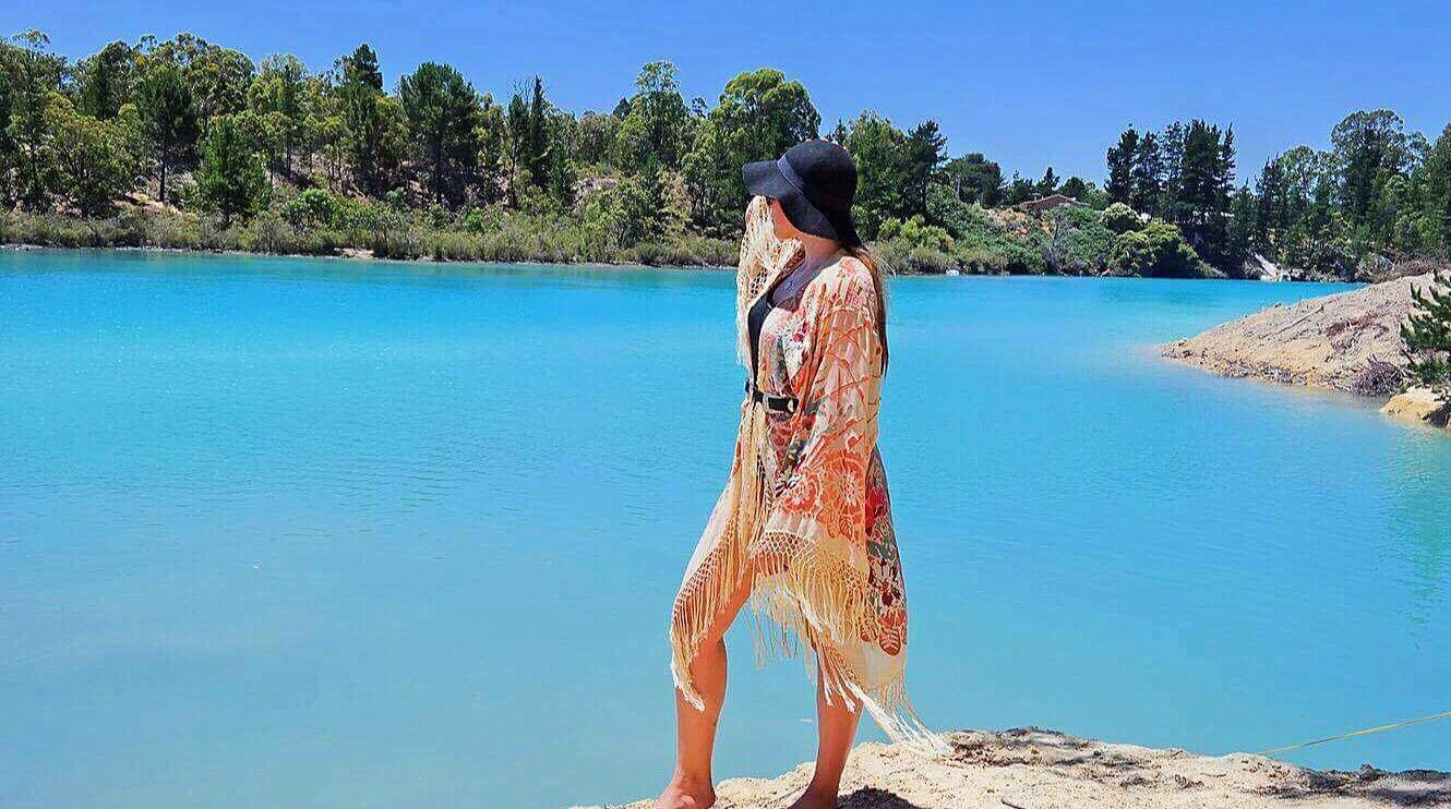 An image of a girl in a kimono and hat looking out to azure blue waters of Black Diamond Lake