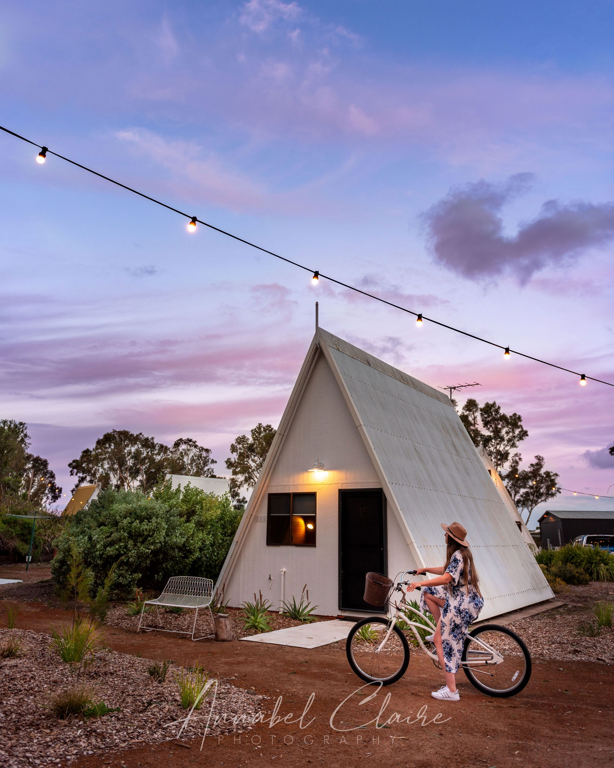 girl rides bike in front of Aframe house to show accommodation at Esperance Chalet Village while driving the south west edge